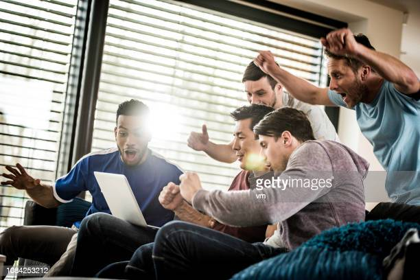 excited friends cheering while watching sports match on a laptop - american football sport stock pictures, royalty-free photos & images