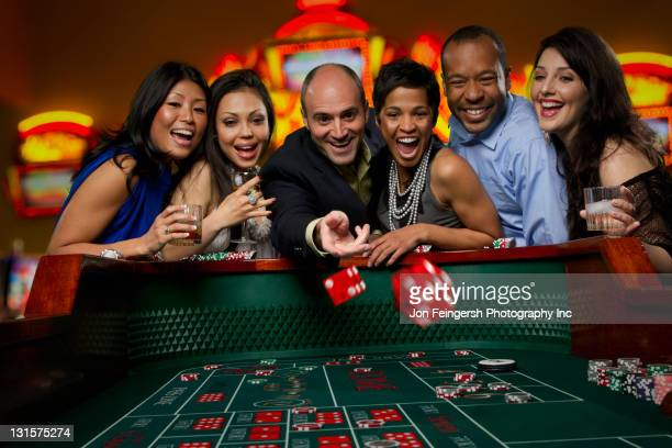 excited friends gambling at craps table in casino - casino stock pictures, royalty-free photos & images