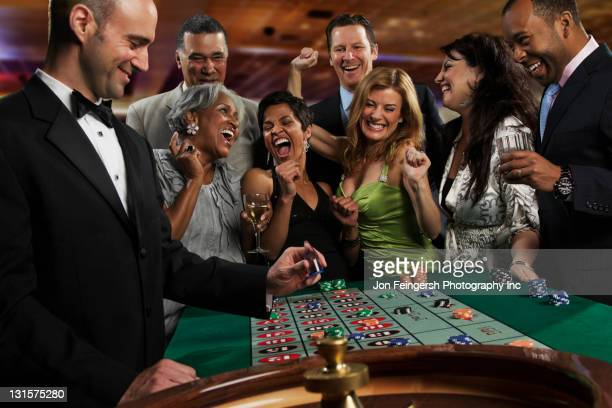 excited friends gambling at roulette table in casino - casino stock pictures, royalty-free photos & images