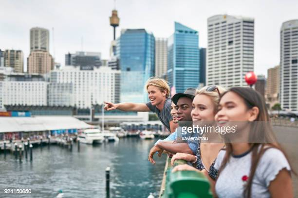 excited friends looking away against buildings - tourism stock pictures, royalty-free photos & images