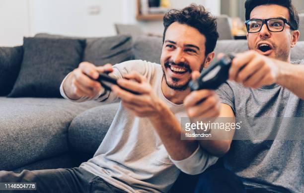 aufgeregte freunde beim spielen von videospielen - computerspiel konsole stock-fotos und bilder