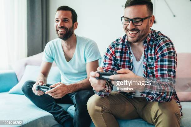 excited friends playing video games - man cave stock pictures, royalty-free photos & images