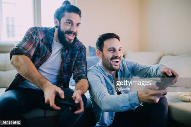 excited friends playing video games - gamer stock pictures, royalty-free photos & images