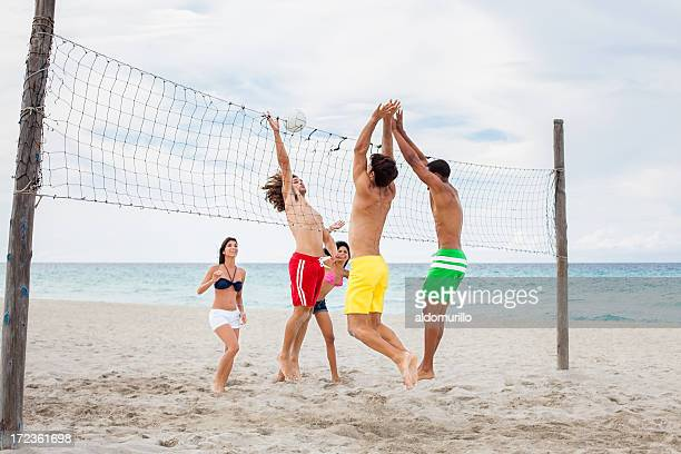 Excited friends playing volleyball