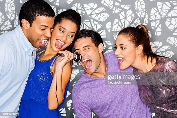 Begeistert Freunde zusammen singen Karaoke im Nightclub