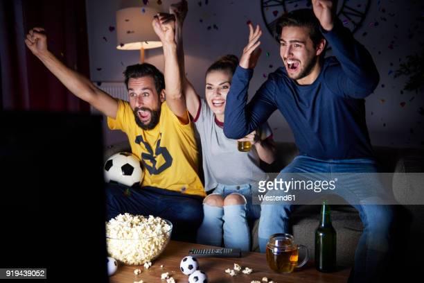 excited friends sitting on the sofa watching tv - fan stock-fotos und bilder