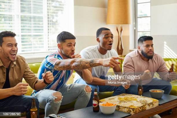 Excited friends watching match on TV at home