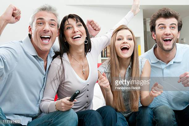 Excited friends watching sport on TV