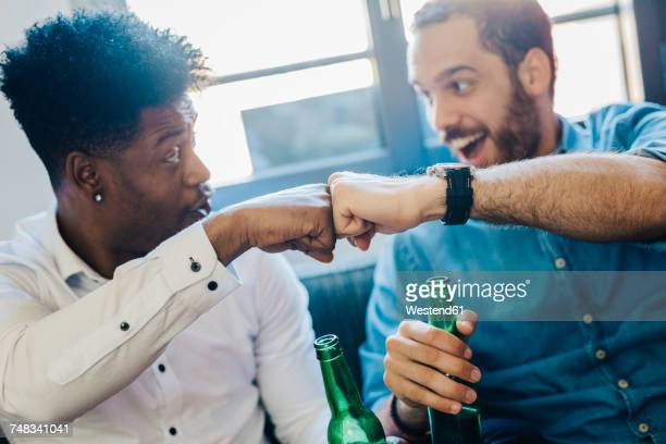 excited friends with beer bottles sitting on the sofa bumping fists - fist bump stock pictures, royalty-free photos & images