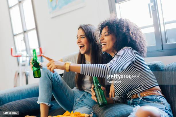 Excited friends with beer bottles sitting on the sofa watching TV