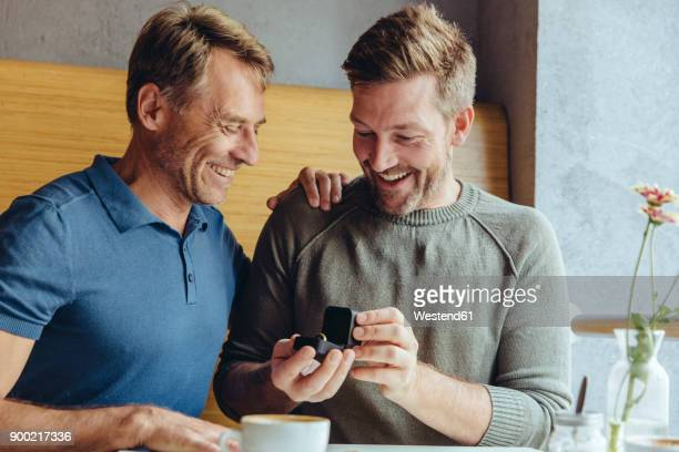 Excited gay couple with wedding ring in cafe