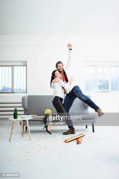 excited german football fan couple cheering - watch what happens: live stock pictures, royalty-free photos & images