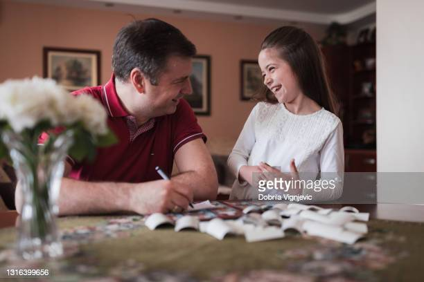 excited girl collecting trading cards with her dad - final game stock pictures, royalty-free photos & images