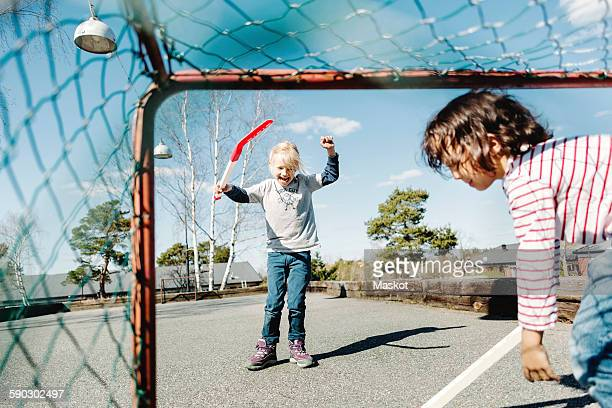 Excited girl gesturing while playing hockey with boy at yard