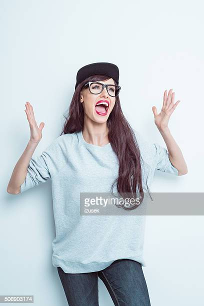 Excited girl in contemporary outfit raising hands and shouting