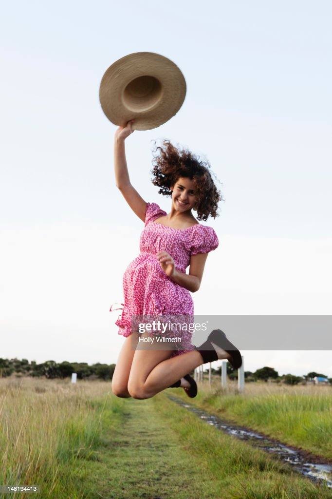 Excited girl jumping in field : Stock Photo