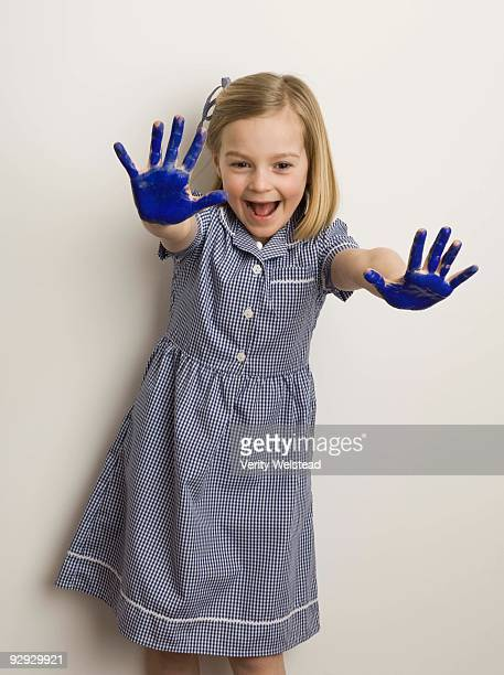 Excited girl showing hands covered with paint