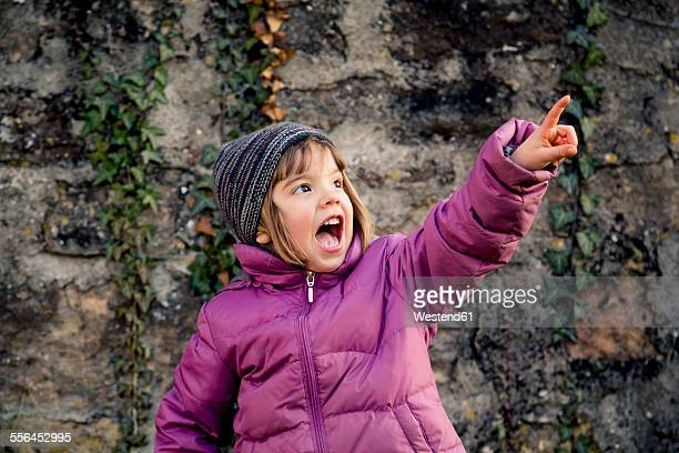 Excited girl wearing woolly hat and pink winter jacket pointing at something