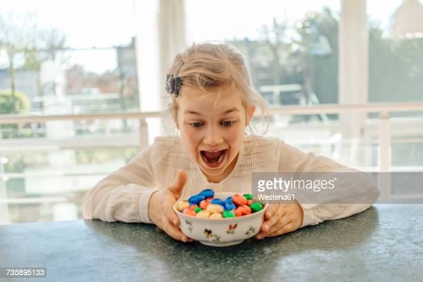 Excited girl with chocolate Easter eggs on table
