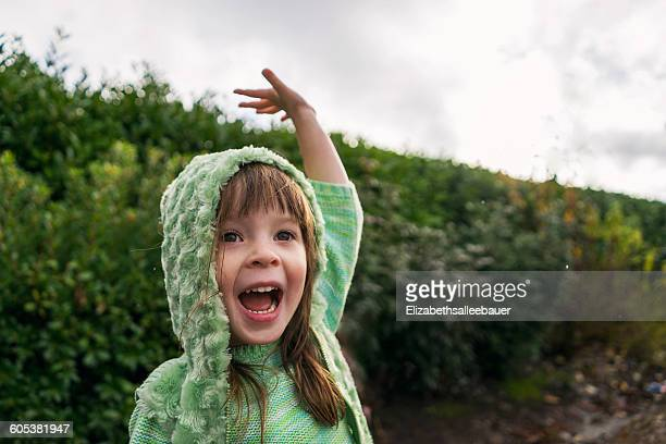 Excited girl with raised arm in the rain