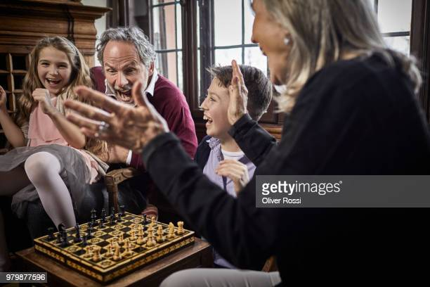 excited grandparents playing chess with grandchildren - prosperity stock pictures, royalty-free photos & images