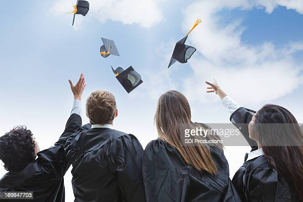 excited group of college graduates throwing their hats in celebration - graduation gown stock pictures, royalty-free photos & images