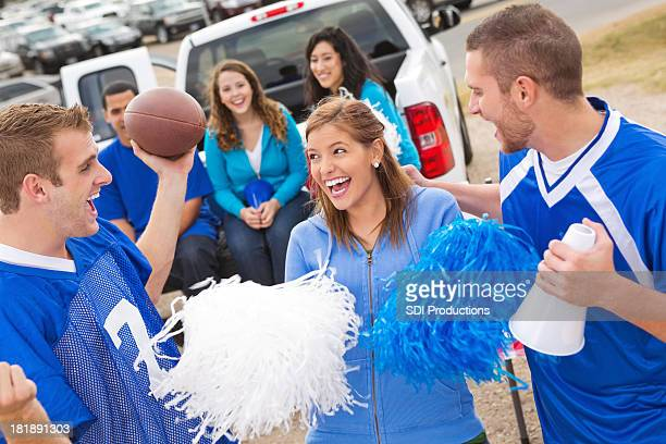Excited group of friends tailgating at college football stadium