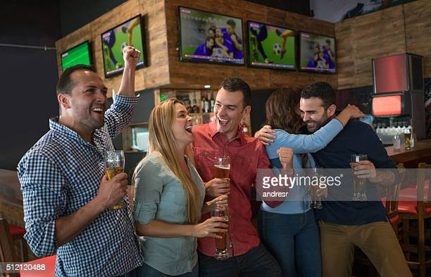 Excited group of people watching football at a bar