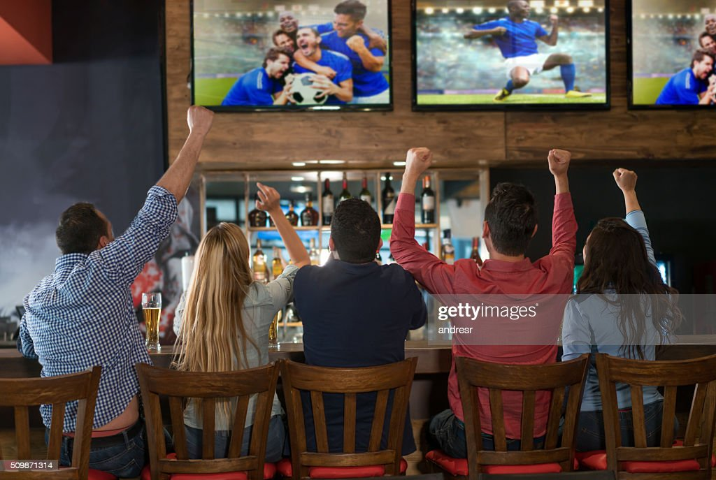 Excited group of people watching the game at a bar : Stock Photo