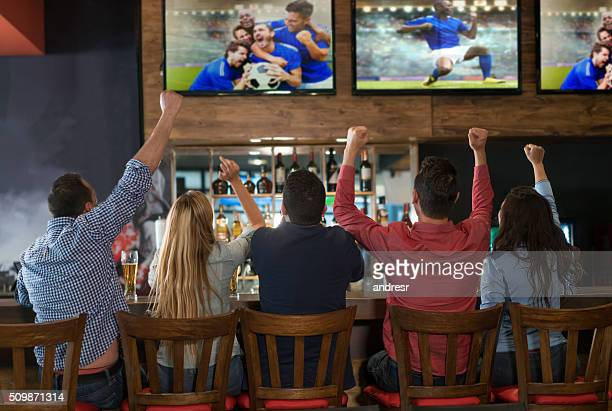 excited group of people watching the game at a bar - calcio sport foto e immagini stock