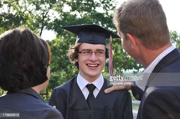 Entusiasmado High School graduação em pé com os seus pais