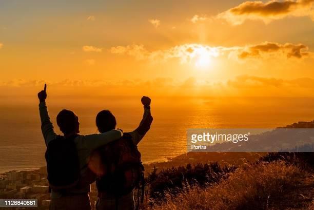 日没の間に海に対して丘で興奮したハイカー - 若い男性だけ ストックフォトと画像