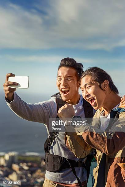 Excited hikers taking selfie through mobile phone
