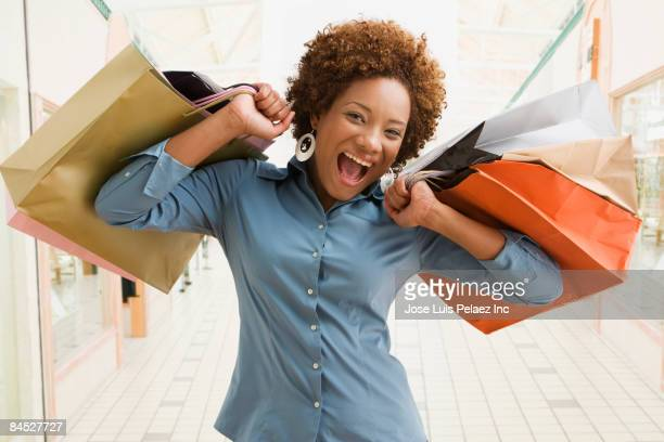 excited hispanic woman holding shopping bags - medium group of objects stock pictures, royalty-free photos & images