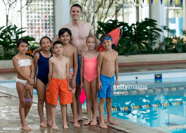 Excited kids ready to get into the pool for their swimming lesson and instructor standing behind them holding a rescue buoy all looking at camera smiling
