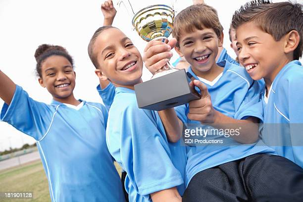 Excited kids' soccer team celebrating win with trophy