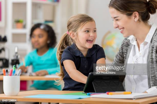 Excited kindergarten student uses digital tablet at school