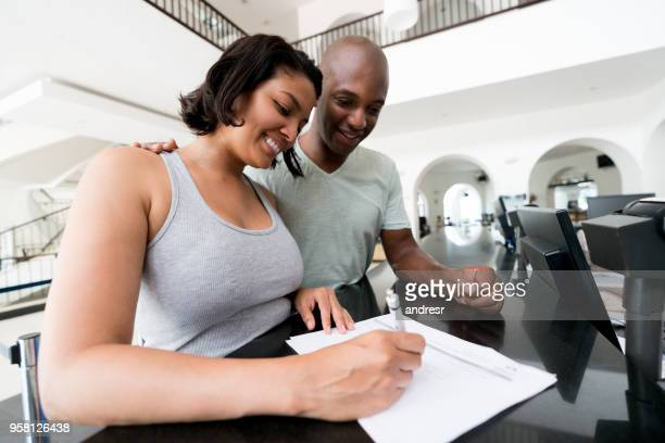 Excited latin american diverse couple checking into hotel filling in a form both looking very happy