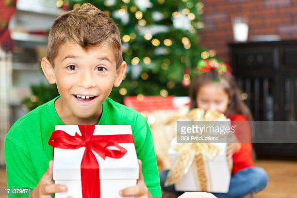Excited little boy opening Christmas presents with sister