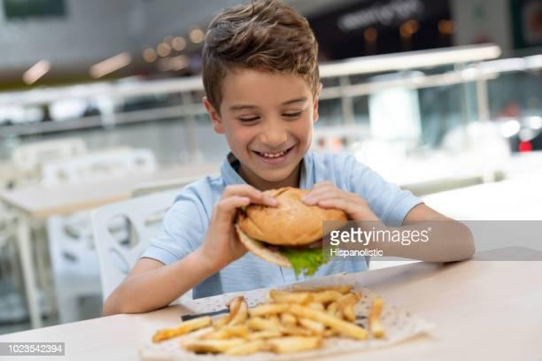 heureux petit garçon prêt à profiter d'un délicieux burger et des frites à l'aire de restauration dans un centre commercial - repas servi photos et images de collection