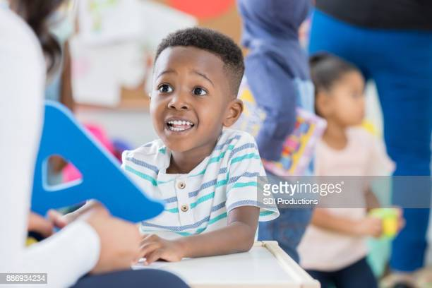 Excited little boy recognizes letter A at preschool