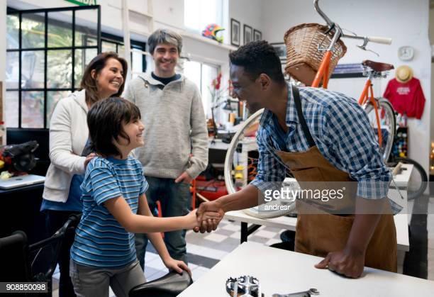 Begeistert kleine Junge schüttelte die Hand der Verkäufer bei einem Fahrrad-Geschäft und die Familie suchen glücklich