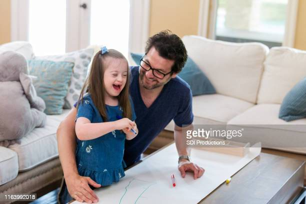 excited little girl and her dad coloring together - down syndrome stock pictures, royalty-free photos & images
