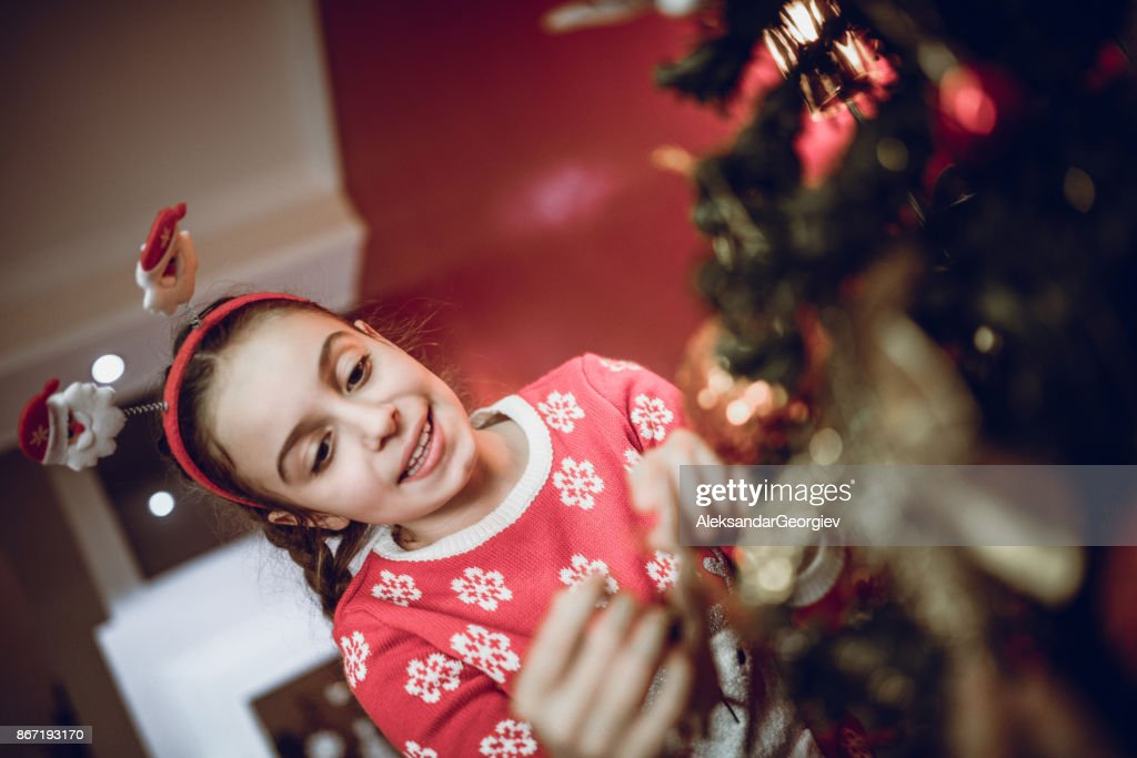 excited little girl decorate her fir tree with christmas ornaments