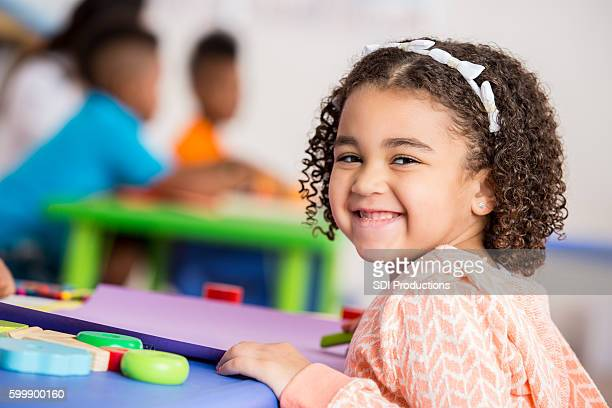 Excited little girl in daycare classroom