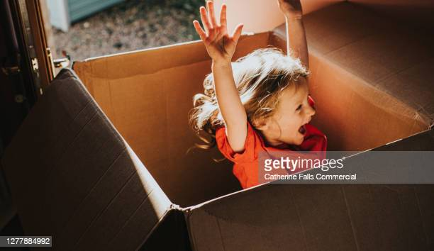 excited little girl jumping inside a huge cardboard box - carefree stock pictures, royalty-free photos & images
