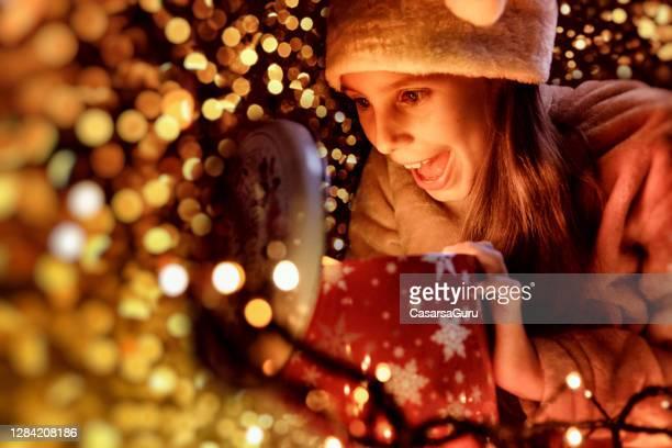 夜に彼女のクリスマスプレゼントを見て興奮した小さな女の子 - ギフトラウンジ ストックフォトと画像