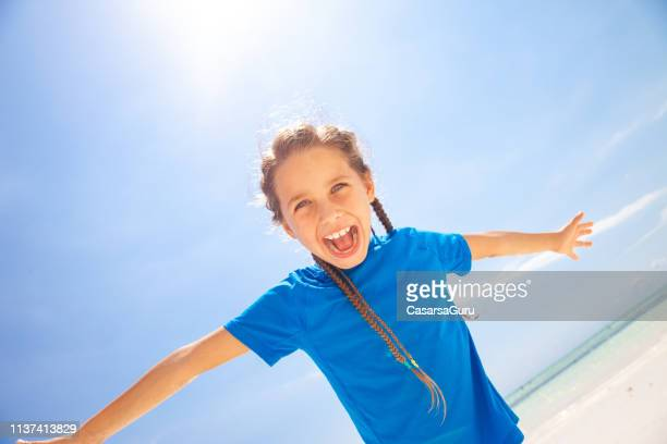 excited little girl on bach vacation - human arm stock pictures, royalty-free photos & images