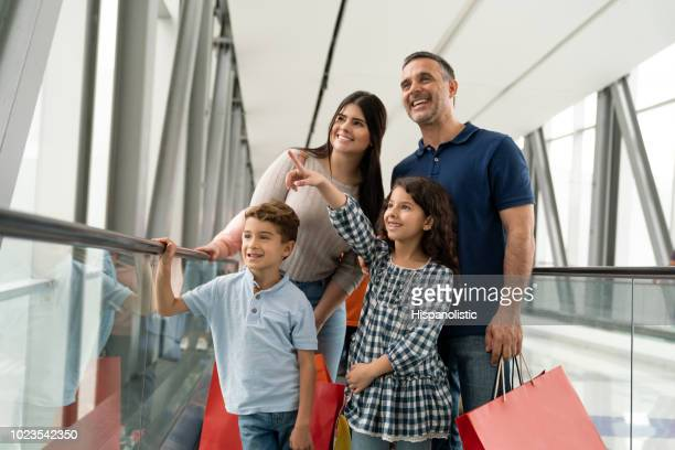 excited little girl pointing away while they are on the moving walkway at the airport - travolator stock pictures, royalty-free photos & images
