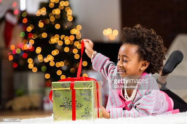 Heureuse petite fille en levant ruban de Déballer un cadeau de Noël